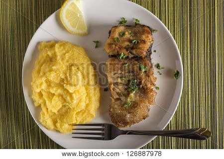 Delicious plate of fresh fried carp with polenta
