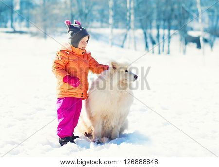 Child With White Samoyed Dog On Snow In Park Winter
