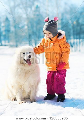 Smiling Child With White Samoyed Dog On Snow In Winter Park