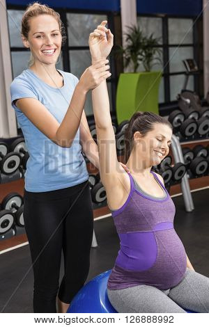 Trainer helping pregnant woman exercising on an exercise ball at the gym