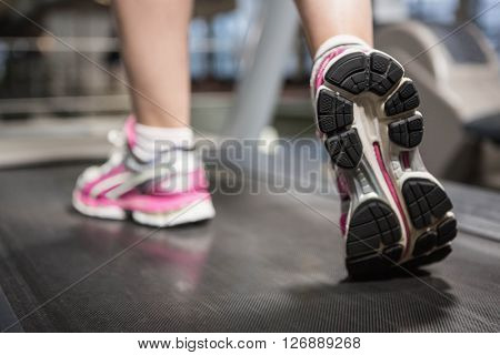 Feet of a woman on a treadmill in a gym