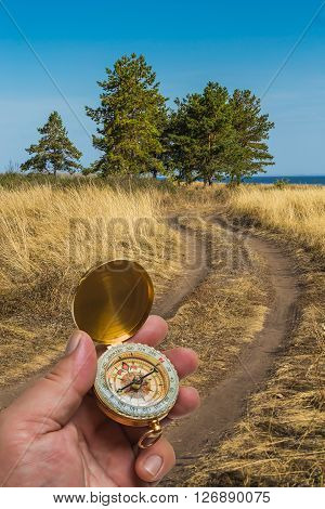 man holding a compass on the background of the road field and trees
