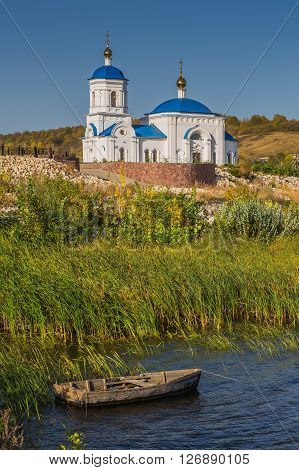 Boat On The River Against Background Of Orthodox Church
