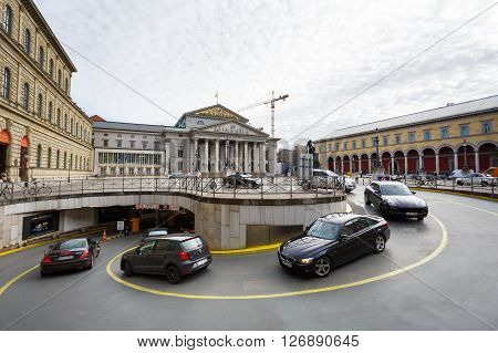 Munich Germany - January 03 2016: The cars drives into the underground parking on the Odeon square on the background of Bavarian State Theater