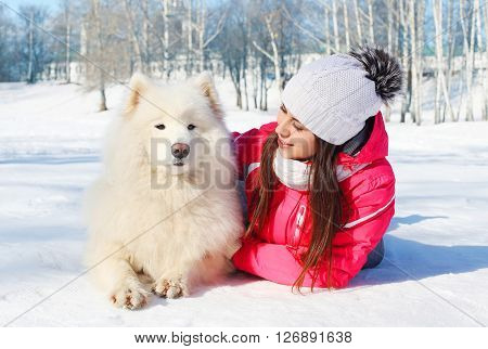 Portrait Woman Owner With White Samoyed Dog Lying On Snow In Winter Day