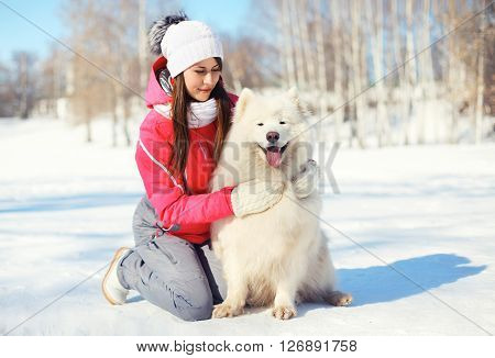 Woman Owner Hugging White Samoyed Dog On Snow In Winter Day
