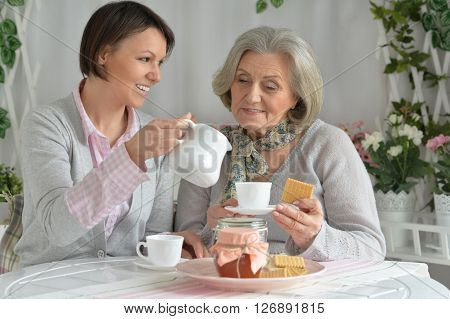 Senior woman with daughter  with tea and food