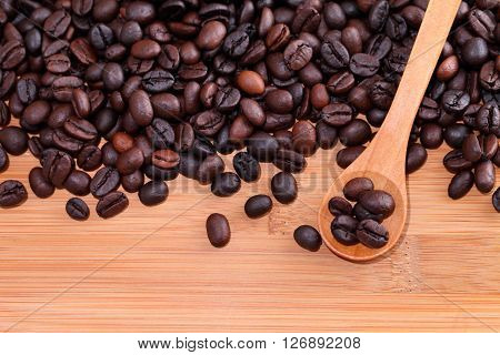 Coffee on grunge wooden background ,Coffee bean on spoon wooden.