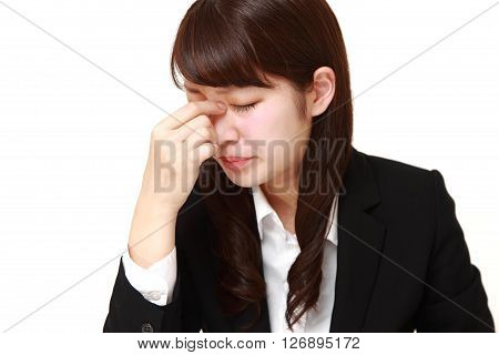 young Japanese businesswoman suffers from Asthenopia on white background