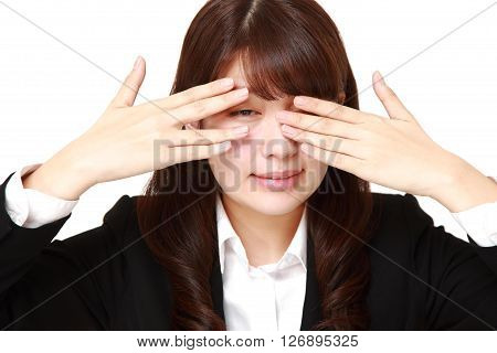 businesswoman covering her face with hands peeping at the camera through her fingers