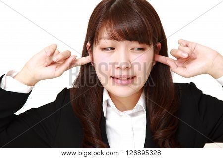 studio shot of Young Japanese businesswoman suffers from noise