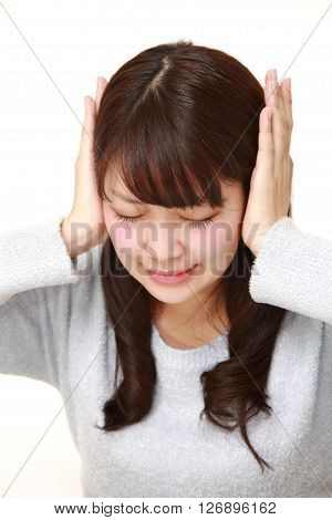 studio shot of  Young Japanese woman suffers from noise on white background