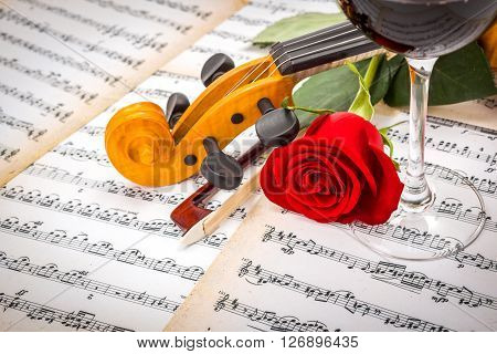 Close View Of Violin Scroll, Bow, Red Rose And Wine