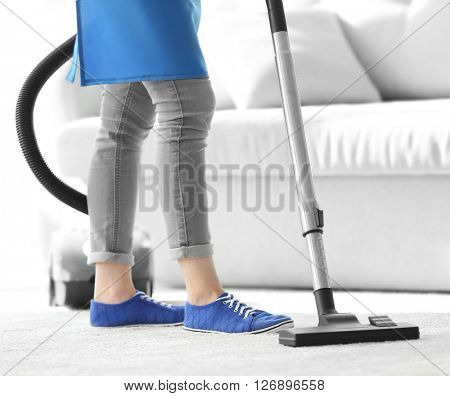 Cleaning concept. Young woman cleaning carpet with vacuum cleaner, close up