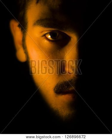 Half a man's face is closed by the shadow.