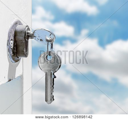 Keys in a lock with blue sky background.