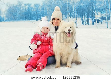 Mother and baby with white Samoyed dog together in winter day
