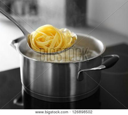 Boiling nest pasta in pan on electric stove in the kitchen