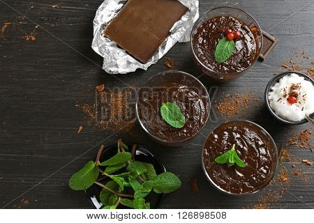 Glass cups of chocolate dessert with fresh mint and frothed milk on black wooden table
