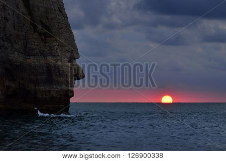 Cliff Resembling Human Head Looking At An Ocean Sunset