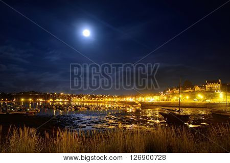 Midnight view of the port of Camaret sur mer France with rows of yachts on anchorage orange lanterns and full moon