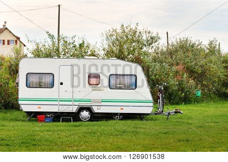Caravan trailer on a green lawn under the trees. France