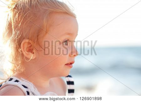 Cute baby girl 2-3 year old posing over sea background outdoors. Looking away closeup.