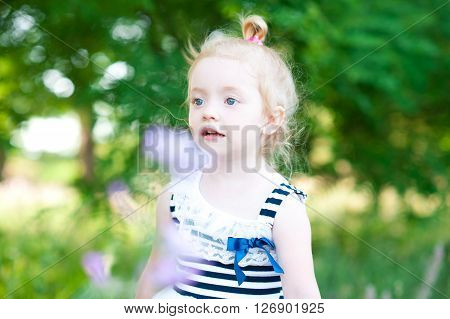 Cute baby girl 2-3 year old walking in meadow. Looking away. Posing outdoors. Wearing striped trendy dress. Childhood.