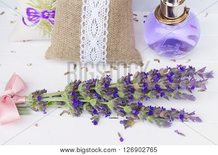 Lavender herbal water with fresh and dry flowers on white wood