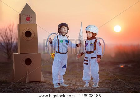 Two adorable children boy brothers playing in park on sunset dressed like astronauts imagining they are flying on the moon