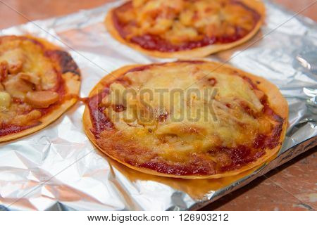 Close up of chicken ham cheese crispy pizza bake in oven made with halal ingredient for muslim.