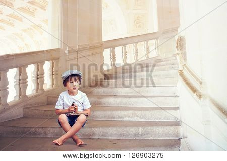 Adorable Little Barefoot Boy, Sitting On A Beautiful Staircase With Book And A Big Key