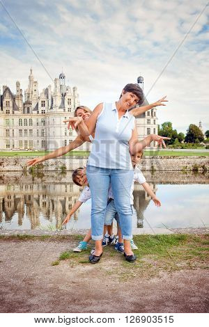 Grandmother mother and two children boys brothers having fun in front of the Chambord castle chateaux on Loire river France