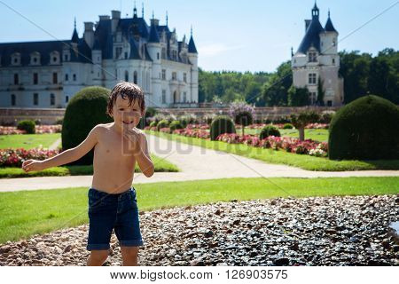 Cute Little Boy, Playing In The Rain In Front Of A Castle In France