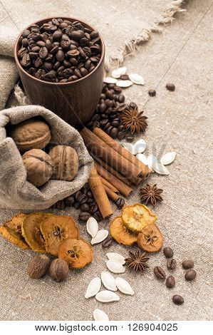 Coffee beans in a clay cup next to nuts and dried fruits