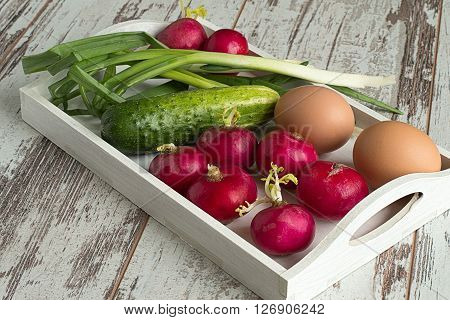 Spring vegetables and eggs on a white tray on a light wooden background.