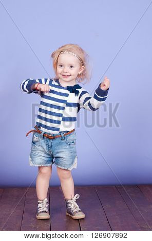 Funny little kids girl 2-3 year old dancing in room over purple. wearing stylish striped shirt and denim shorts. Childhood.