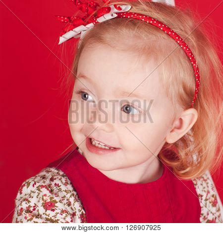 Smiling kid girl 2-3 year old looking away over red. Wearing stylish accessories. Childhood. Closeup portrait.
