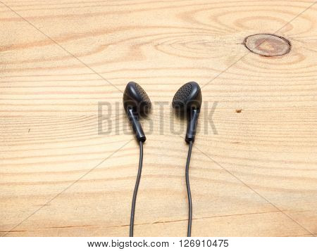 Small black wired earphones lying on a wooden board