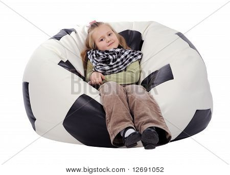 Girl Sitting On An Inflatable Chair In The Form Of A Soccer Ball, Isolated
