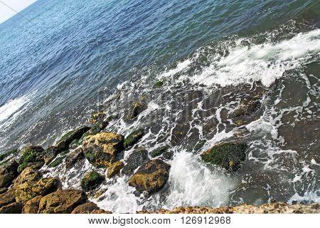 Sea waves breaking on coastal rocks and foaming