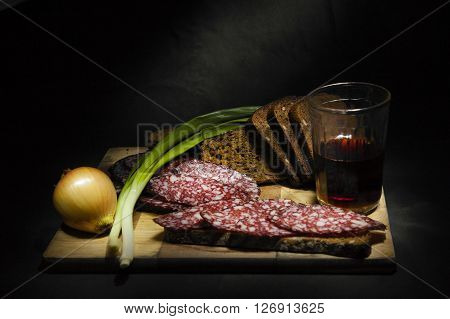 Bow, bread, tincture in a glass and sausag on wooden cutting Board