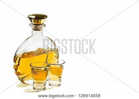 Bottle and two shot glasses of tequila on a white background