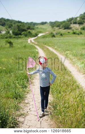 child with a butterfly net   is on the trail