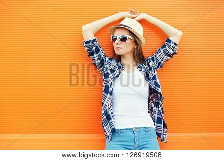 Fashion Pretty Woman Wearing A Straw Hat And Sunglasses Over Orange Background