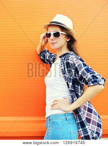 Pretty Woman Wearing A Straw Hat And Sunglasses Over Orange Background