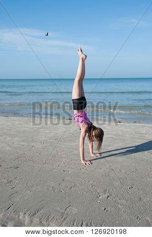 Girl doing gymnastic exercises on the beach, Florida, USA