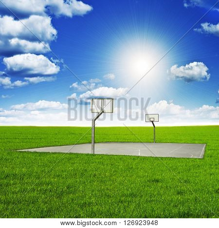 Basketball court amidst beautiful scenery with blue sky and sun