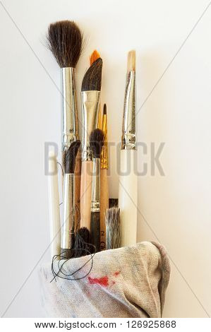 Painting brushes wrapped in a rag on a white background. Close up top view.