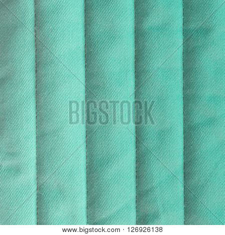 Pastel turquoise quilted textiles with insulation. Vertical stripes. Close up fragment of the top view.